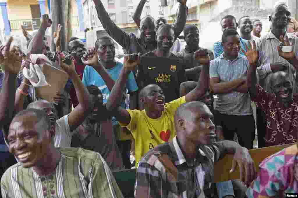Para pendukung calon presiden Muhammadu Buhari bersorak saat menonton hasil pemilu di sebuah jalan di Lagos (31/3). (Reuters/Joe Penney)