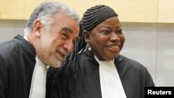 Newly sworn-in ICC prosecutor Fatou Bensouda shares a laugh with her predecessor Luis Moreno-Ocampo (L) at the ICC, The Hague, Netherlands, June 15, 2012.