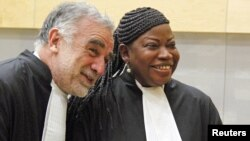 ICC prosecutor Fatou Bensouda shares a laugh with her predecessor Luis Moreno-Ocampo (L) at the ICC, The Hague, Netherlands, June 15, 2012.