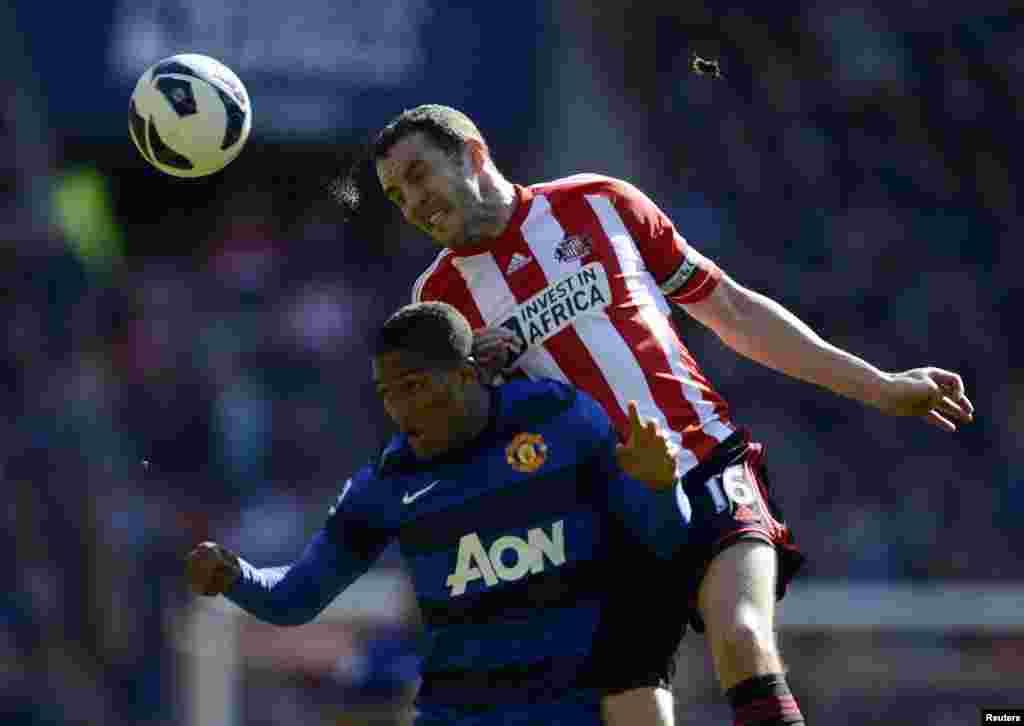 Cầu thủ John O'Shea (phải) của đội Sunderland tranh bóng với cầu thủ Antonio Valencia của đội Manchester United trong một trận đấu của giải Ngoại hạng Anh ở Sunderland, miền bắc nước Anh.