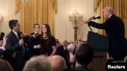 FILE - A White House staff member reaches for the microphone held by CNN's Jim Acosta as he questions President Donald Trump.