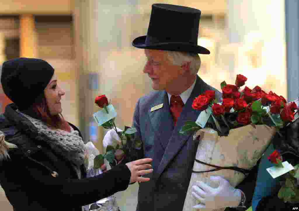 "Self-styled ""Knight of the Rose"" Rolf Schrader offers roses to women in Magdeburg, eastern Germany, on Women's Day."