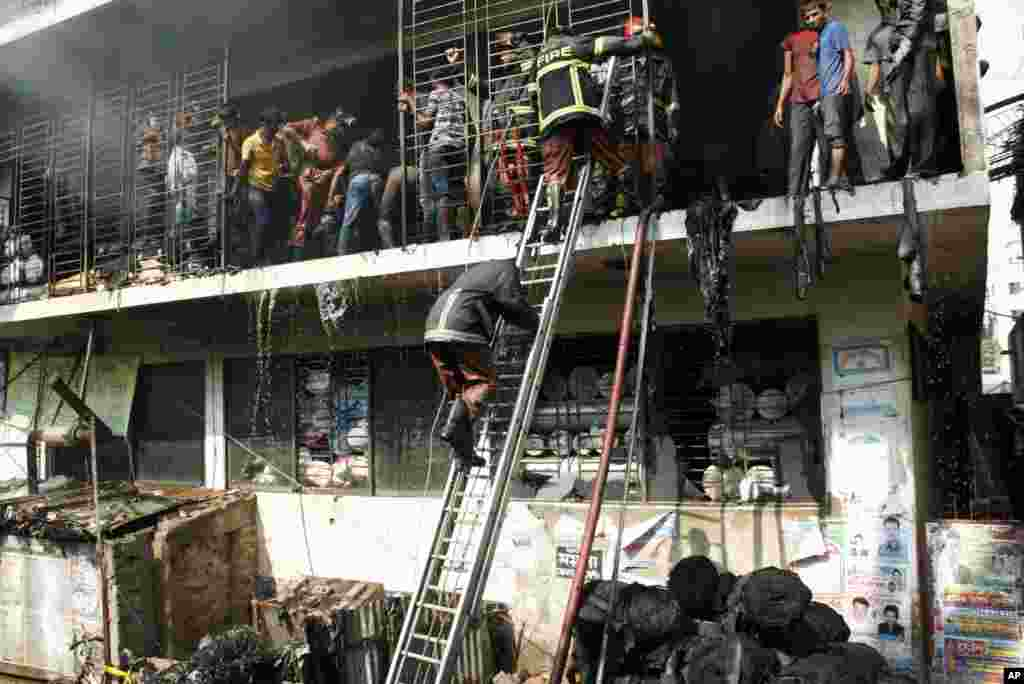 Bangladeshi firefighters and workers try to douse the fire at a garment-factory in Dhaka, Bangladesh, after a similar incident killed more than 100 people on the outskirts of the city, November 26, 2012.