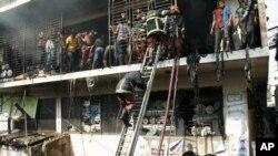 Lính cứu hỏa Bangladesh cố gắng để dập tắt đám cháy tại một nhà máy may ở Dhaka, Bangladesh, hai ngày sau khi một sự cố tương tự đã giết chết hơn 110 người ở vùng ngoại ô của thành phố, ngày 26 tháng 11, 2012.