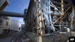 The crippled Fukushima Dai-ichi nuclear power station is seen through a bus window in Okuma, Japan Saturday, Nov. 12, 2011. Media allowed into Japan's tsunami-damaged nuclear power plant for the first time Saturday saw a striking scene of devastation: twi