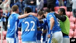Tim sepak bola Wigan merayakan kemenangan atas Newcastle, Sabtu (28/4).