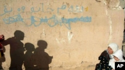 "A northern Iraqi woman sits in front of her house with her four children, in the bordertown of Chamchamal, Iraq, March 30, 2003. Writing on wall reads: ""This house is for sale."""