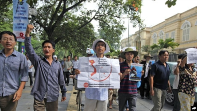 Protesters hold anti-China placards to protest what they say is aggressive action by China in the dispute over a resource-rich area in the South China Sea, while marching near the Chinese embassy in Hanoi, Vietnam, July 10, 2011
