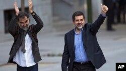 Los dirigentes Jordi Cuixart, izquierda, y Jordi Sánchez, saludan a sus simpatizantes a la llegada a un tribunal en Madrid. Posteriormente fueron encarcelados.