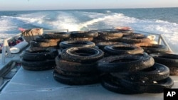 This Oct. 12, 2017, photo provided by the California Coastal Commission/UC Davis shows a pile of scrap tires after they were pulled out of the water off Balboa Peninsula in Newport Beach, Calif.