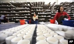 FILE - Workers coat potteries with enamel in a factory in Bat Trang village, Hanoi, Vietnam.