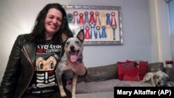 In this Thursday, January 31, 2019, photo Lisa Topol poses for a photo with her two rescue dogs, Schmutzy, right, and Plop, in New York. Topol recently had the DNA tested for both dogs.
