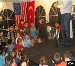 Anak-anak dihibur dengan permainan panggung boneka.