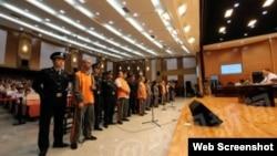 中國官方媒體公布的庭審照片中,嫌疑人站成一排,接受審判。(網絡圖片)