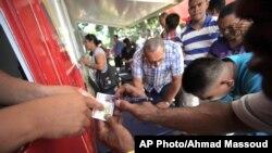 Ciudadanos venezolanos obtienen identificaciones que les permitirán votar este domingo en las elecciones presidenciales.