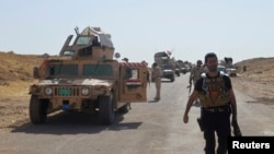 FILE - Military vehicles of Iraqi security forces on a road during clashes with Islamic State (IS) militants in the Hamrin mountains in Diyala province.