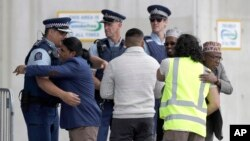 A police officer embraces a man as he arrives for Friday prayers at an arena in Christchurch, New Zealand, Friday, March 13, 2020. Events to mark the death of 51 people who were killed and dozens more injured when a gunman attacked the two mosques. (AP Photo/Mark Baker)