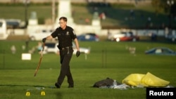 Seorang polisi membawa ikat pinggang sebagai bukti di lokasi seorang laki-laki membakar dirinya di Monumen Nasional, Washington DC (4/10). (Reuters/Gary Cameron)