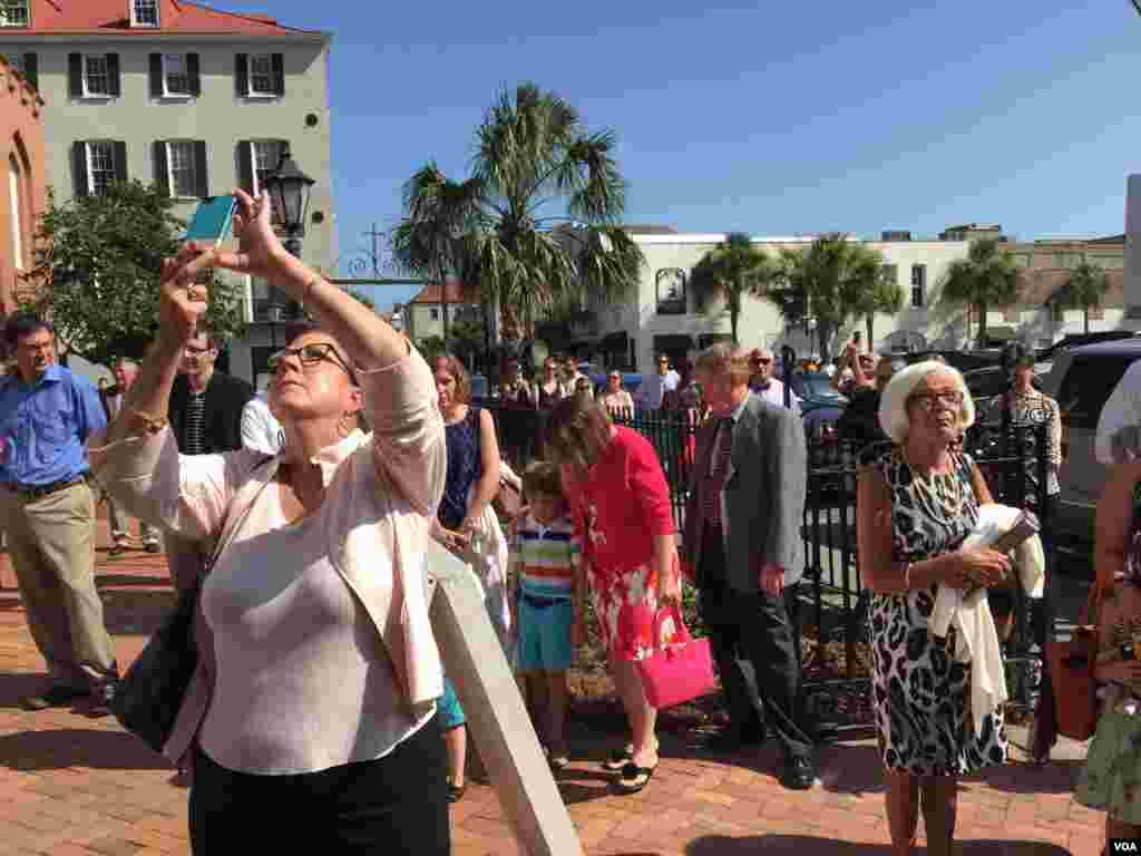 People stop to listen as church bells ring out across Charleston, South Carolina, June 21, 2015. (Jerome Socolovsky/VOA)