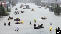 Rescue boats fill a flooded street as flood victims are evacuated during Tropical Storm Harvey in Houston, , Aug. 28, 2017.