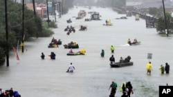 Rescue boats fill a flooded street as flood victims are evacuated during Tropical Storm Harvey, Aug. 28, 2017, in Houston.