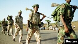 Eritrean soldiers march past displaced civilians as they redeploy near the town of Adi Quala on June 2.