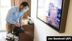 In this Monday, July 6, 2020 photograph, an employee wearing a mask due to the coronavirus pandemic fogs disinfectant in a hotel room at the Rove City Centre Hotel in Dubai, United Arab Emirates.