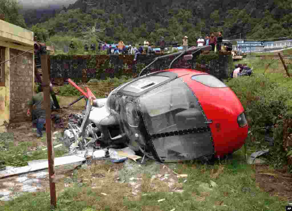Nepalese look at a helicopter that crashed in Lukla. The helicopter crashed while attempting to land near Mount Everest, injuring all four people on board, Nepalese police said.