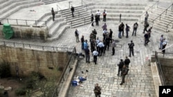 Polisi Israel berdiri di dekat jenazah warga Palestina, yang menurut polisi setempat menikam dua petugas kepolisian, sebelum ditembak mati polisi lainnya di Pintu Gerbang Damaskus di kota tua Yerusalem (10/10). Hari Senin (12/10) seorang pria dilaporkan berusaha menikan seorang polisi Israel di dekat Lions Gate, Yerusalem.