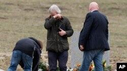 Thân nhân bật khóc trong lúc đặt hoa tại một phiến đá được dựng lên như một đài tưởng niệm các nạn nhân vụ rớt máy bay tại Le Vernet, Pháp, ngày 28/3/2015.