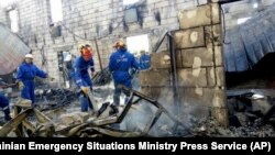 Сотрудники министерства по чрезвычайным ситуациям обследуют место пожара. Леточки. Украина. 29 мая 2016 г.