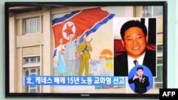 Đài truyền hình Nam Triều Tiên loan tin về ông Kenneth Bea (phải). Phía sau là tòa cao ốc trong thủ đô Bắc Triều Tiên, 2/5/13