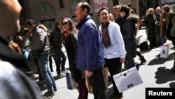 (FILE)Chinese shoppers stand with shopping bags on a sidewalk along 5th Avenue in New York City, April 4, 2013. Chinese tourists, known for traveling in organized tours and snapping up luxury fashion abroad, spent $102 billion on foreign trips last year,