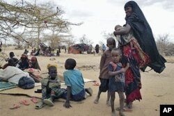 FILE - Refugees rest outside in an open area as there is lack of tents at the Dollo Ado refugee camp, Ethiopia, July 7, 2011.