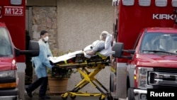 Medical workers push a man on a stretcher into an ambulance at the Life Care Center of Kirkland, a long-term care facility linked to several confirmed coronavirus cases, in Kirkland, Washington, U.S. March 3, 2020.