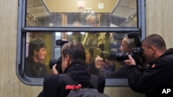 FILE - Musician Markus Rindt a 1989 German refugee is surrounded by media after boarding a train in Prague, Czech Republic, Oct. 1, 2009. (AP Photo/Petr David Josek)