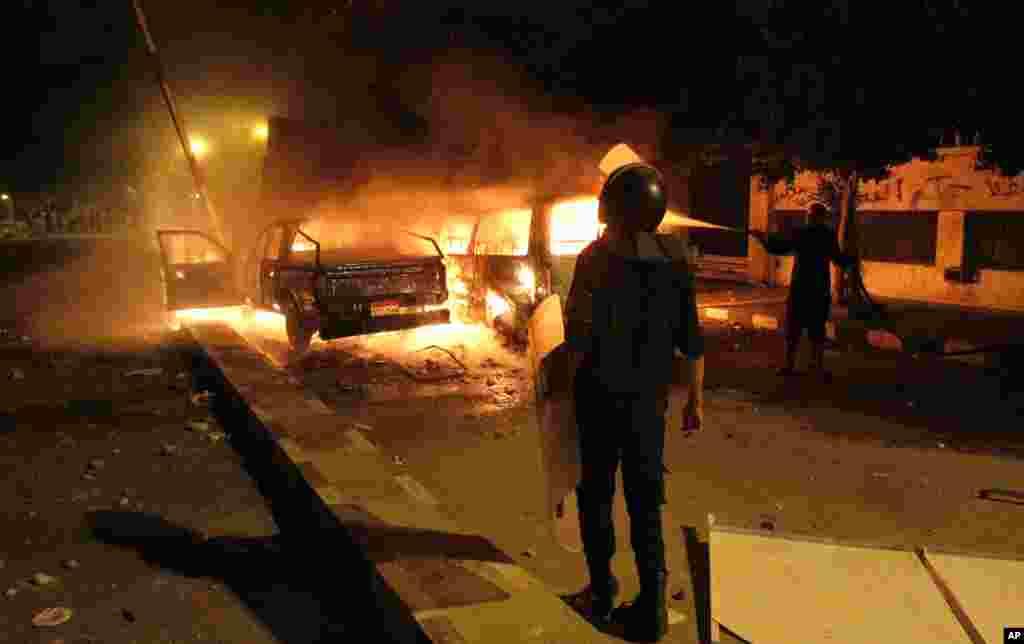 یک پلیس در برابر خودرو پلیس که معترضین آنرا در برابر سفارت امریکا در قاهره به آتش کشیدند ایستاده است.