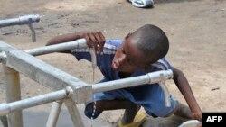 Çeşmeden damlayan suyu içmeye çalışan bir Somalili çocuk