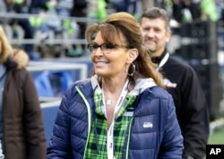 FILE - Sarah Palin, political commentator and former governor of Alaska, walks on the sideline before an NFL football game between the Seattle Seahawks and the Los Angeles Rams, in Seattle, Dec. 15, 2016. Palin's spokesman told The Associated Press Thursday that reports that she was in a coma following a car accident are not true.