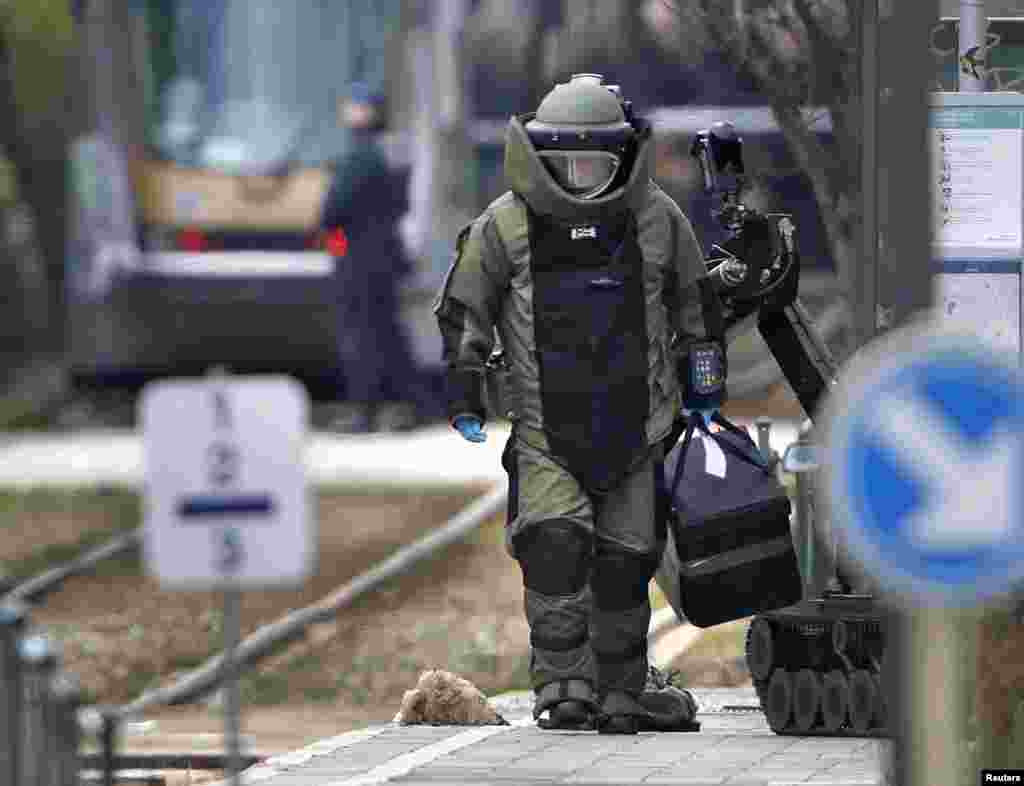 A bomb disposal expert takes part in a search in the Brussels borough of Schaerbeek following Tuesday's bombings in Brussels, Belgium.