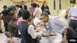 Presiden Amerika Barack Obama, mendengarkan seorang anak selagi memmbantu dalam acara Thanksgiving di Martha's Table, sebuah toko makanan di Washington.