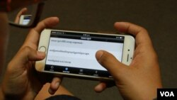 """A user explores """"Cambodian Voter's Voice"""", a new mobile app developed by Cambodia's election watchdog COMFREL, on August 27, 2015. (Hean Socheata/VOA Khmer)"""