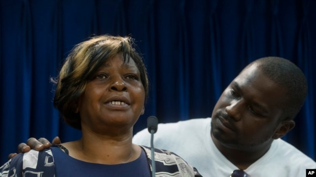FILE - Audrey DuBose, mother of Samuel DuBose, is comforted by her son Aubrey as she speaks to the media after murder and manslaughter charges against University of Cincinnati police officer Ray Tensing were announced for the traffic stop shooting death of her son, July 29, 2015.
