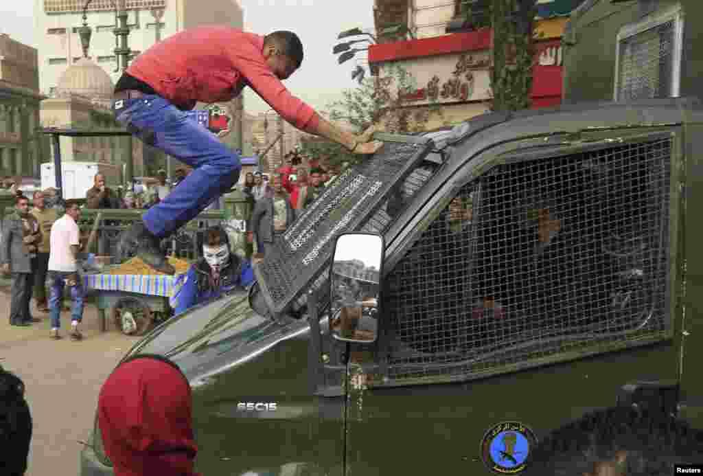 Người biểu tình nhảy lên đập phá xe của cảnh sát trong cuộc biểu tình chống chính phủ ở Cairo, Ai Cập.