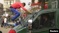 Seorang demonstran melompat ke mobil polisi yang lewat dalam protes anti-pemerintah (22/2). (Foto: Reuters)