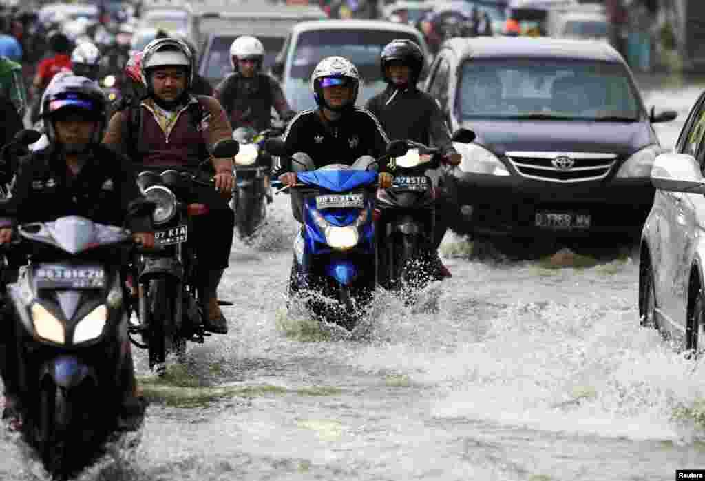 홍수로 인도네시아 자카르타 시내가 범람한 가운데, 사람들이 오토바이를 타고 거리를 지나고 있다.