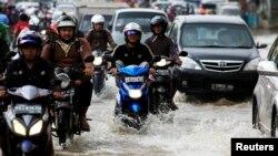 Pengendara motor mengarungi banjir di Jakarta. (Foto: Dok)