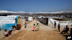 FILE - Refugees from Syria are seen outside their tents, in the town of Saadnayel, east Lebanon, April 23, 2019. Minority Yazidi refugees now face a possible forced return by Lebanese authorities to Syria.