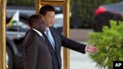 FILE - In this file photo taken on Aug. 25, 2014, Chinese President Xi Jinping, right, shows Zimbabwe's President Robert Mugabe the way during a welcome ceremony outside the Great Hall of the People in Beijing, China.