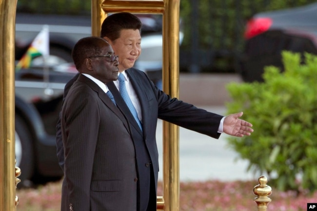 FILE - Chinese President Xi Jinping, right, shows Zimbabwe's former President Robert Mugabe the way during a welcome ceremony outside the Great Hall of the People in Beijing, China, Aug. 25, 2014.